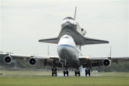 The space shuttle Discovery, riding atop a NASA 747 transport jet, arrives at Dulles International Airport in Virginia April 17, 2012. REUTERS/Gary Cameron