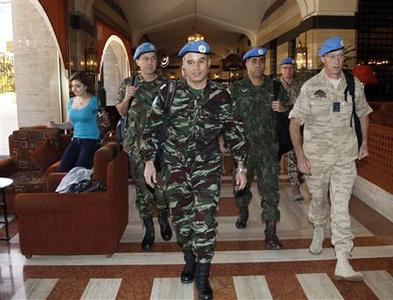 A team of U.N. monitors walk through a hotel in Damascus April 16, 2012. REUTERS/Khaled al- Hariri