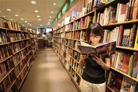 A woman reads a book at bookstore in Shanghai August 13, 2009. REUTERS/Aly Song/Files