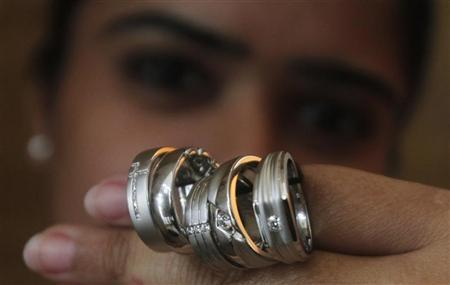 A saleswoman displays platinum rings for the camera at a jewellery showroom in New Delhi April 17, 2012. REUTERS/Parivartan Sharma