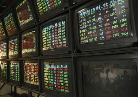 Investors are reflected in a screen showing stock information at a brokerage house in Wuhan, Hubei province August 19, 2011. REUTERS/Stringer