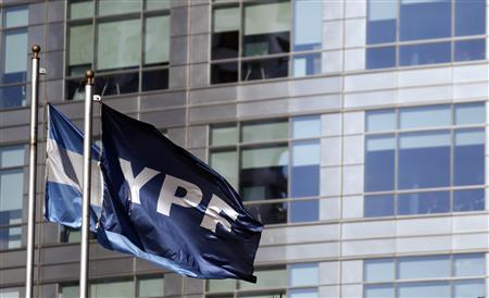 A flag of YPF gas and oil company flutters next to an Argentine flag outside the YPF headquarters in Buenos Aires, April 17, 2012. REUTERS/Marcos Brindicci