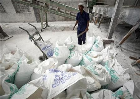 A worker stands behind sacks containing processed sugar crystals inside a sugar factory in Satara district, about 285km south of Mumbai May 10, 2011. REUTERS/Vivek Prakash/Files