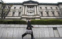 Мужчина проходит мимо Банка Японии в Токио, 24 ноября 2009 года. Банк Японии готов провести дополнительное монетарное смягчение, чтобы помочь экономическому восстановлению и избежать дефляции, сообщил в среду заместитель управляющего центробанка, дав самый сильный намек на дальнейшие стимулы с февральского заседания. REUTERS/Toru Hanai