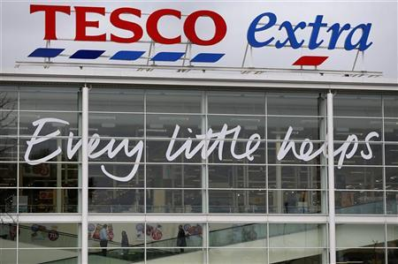 Shoppers travel on an escalator in a Tesco store near Manchester, northern England April 18, 2012. T REUTERS/Phil Noble