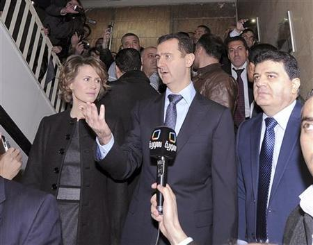 Syria's President Bashar al-Assad and his wife Asma talk to Syrian TV after voting at a referendum on a new constitution at a polling station at a Syrian TV station building in Damascus February 26, 2012, in this handout photograph released by Syria's national news agency SANA. REUTERS/SANA