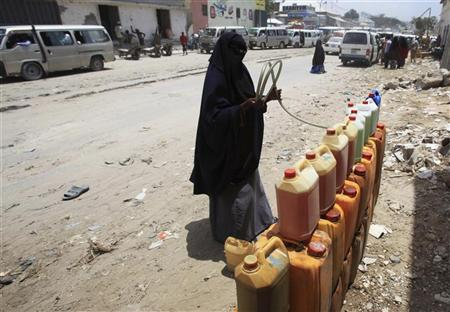 A businesswoman siphons petrol into a jerry can at a makeshift fuel station along a street near the main Baraka market in Mogadishu, March 26, 2012. REUTERS/Ismail Taxta
