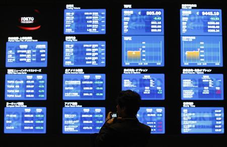 A man takes a photo of displays showing market prices at the Tokyo Stock Exchange in Tokyo April 11, 2012. REUTERS/Toru Hanai