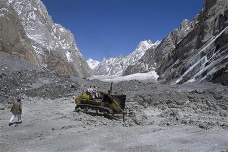 Pakistan soldiers use heavy machinery to dig through the snow at the site of an avalanche in Gayari sector near the Siachen glacier April 18, 2012. REUTERS/Faisal Mahmood