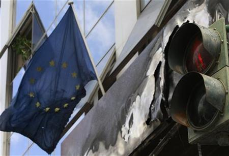 A traffic light is seen next to a burned European Union flag at a branch of the Administrative Reform ministry, which was damaged after a bomb explosion, in Athens April 9, 2012. REUTERS/John Kolesidis