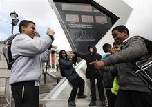 Schoolchildren stand by the Olympic countdown clock in Trafalgar Square marking the 100 day point before the opening ceremony for the London 2012 Olympic Games, London April 18, 2012. REUTERS/Suzanne Plunkett