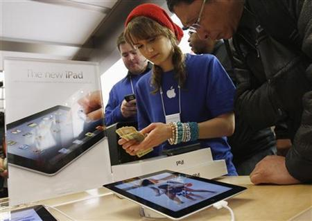 An Apple employee counts money as a customer purchases the newest iPad at the 5th Avenue Apple Store in New York, March 16, 2012. REUTERS/Shannon Stapleton