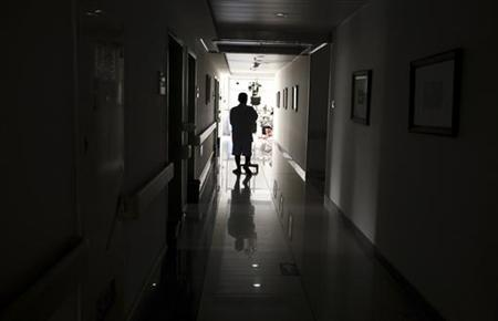 A cancer patient pushes his drip stand as he walks down the hallway of the Beijing Cancer Hospital July 12, 2011. REUTERS/David Gray