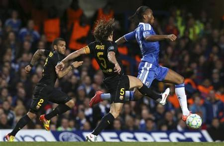 Carles Puyol (C) of Barcelona and Didier Drogba (R) of Chelsea chase the ball during their Champions League semi-final first leg soccer match at Stamford Bridge in London April 18, 2012. REUTERS/Eddie Keogh
