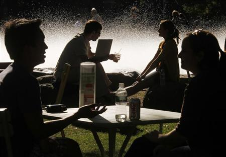 Students and visitors sit in front of a fountain at Harvard University in Cambridge, Massachusetts September 21, 2009. REUTERS/Brian Snyder