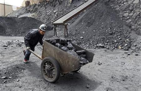 A worker pushes a cart at a coal mine in Pinglu, Shanxi province March 24, 2011. REUTERS/Stringer