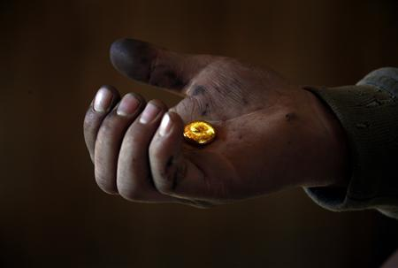 A small-scale miner holds his gold that was melted together at a processing plant located around 100km (62 miles) north of the Mongolian capital city Ulan Bator in this April 5, 2012 file picture. REUTERS/David Gray/Files