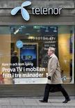 Мужчина проходит мимо отделения Telenor в Стокгольме, 26 октября 2007 года. Федеральная антимонопольная служба РФ оспорила в суде февральскую покупку норвежской Telenor акций Вымпелкома, заявив, что сделка нарушает российское законодательство о стратегических инвестициях, сообщил скандинавский телекоммуникационный оператор в четверг. REUTERS/Bob Strong