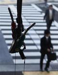 """Люди проходят мимо заправки в Токио, 15 марта 2012 года. Нефть прибавляет в цене в четверг утром, и сорт Brent держится выше $118, хотя инвесторы сохраняют осторожность перед ключевым долговым аукционом Испании, в то время как страхи о новой волне долгового кризиса еврозоны вызывают опасения об уровне спроса на """"черное золото"""".  REUTERS/Toru Hanai"""