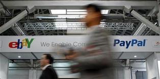Люди проходят мимо баннеров Ebay и PayPal на Мобильном конгрессе в Барселоне, 28 февраля 2012 года. Продажи и прибыль интернет- аукциона eBay Inc оказались лучше ожиданий аналитиков в первом квартале 2012 года, сообщила компания.  REUTERS/Albert Gea