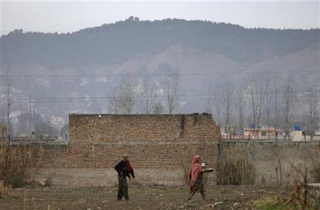Residents walk past the boundary wall of the building where al Qaeda leader Osama bin Laden was killed after it was demolished in Abbottabad February 27, 2012. REUTERS/Faisal Mahmood
