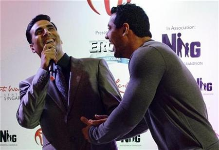Bollywood actors John Abraham (R) and Akshay Kumar share a light moment at the world premiere of 'Housefull 2: The Dirty Dozen' at the Resorts World Sentosa in Singapore April 3, 2012. REUTERS/Tim Chong