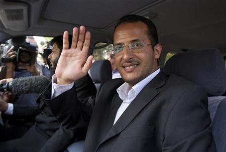 Zakarya Ahmad Al-Fattah, brother of Osama bin Laden's youngest widow, Yemen-born Amal Al-Sadeh, waves to the media after attending court proceedings at a house where bin Laden's family is believed to be detained in Islamabad April 2, 2012. REUTERS/Faisal Mahmood