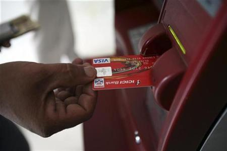 A customer uses his card to withdraw money from an ATM in Jammu October 14, 2008. REUTERS/Amit Gupta/Files