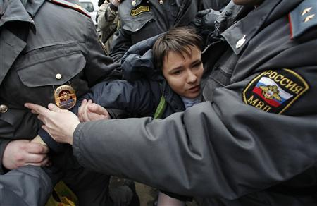 Police officers detain a supporter of punk band ''Pussy Riot'' in front of a court building in Moscow, April 19, 2012. REUTERS/Maxim Shemetov