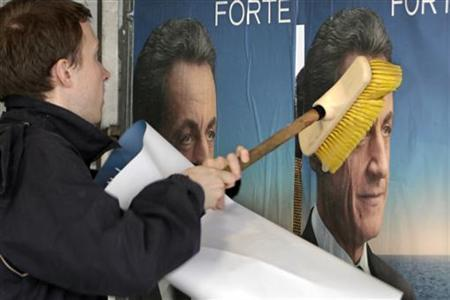 A UMP party activist glue election campaign posters in support of Nicolas Sarkozy, France's President and UMP party candidate for the 2012 French presidential election, on an official board in Paris April 13, 2012. REUTERS/Charles Platiau