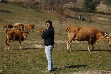 Jose Diogo, 27, poses with his cows near Sao Pedro do Sud, in central Portugal March 2, 2012. REUTERS/Rafael Marchante
