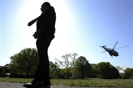 A Secret Service agent stands guard as U.S. President Barack Obama departs on the Marine One helicopter for travel to Colombia for the Summit of Americas, from the White House in Washington April 13, 2012. REUTERS/Jonathan Ernst