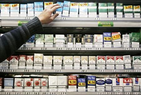 A shopkeeper reaches for a packet of cigarettes in a news stand in London March 5, 2008. REUTERS/Luke MacGregor/Files