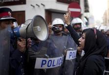 Zaynab, filha do ativista de direitos humanos Abdulhadi al-Khawaja, do Bahrein, faz o sinal de vitória em direção a polícia durante uma manifestação anti-governo para exigir sua libertação, em Manama.  As preocupações com a segurança no Grande Prêmio de Fórmula 1 do Barein, que será realizado no domingo, aumentaram depois de um ataque com bomba. 18/04/2012 REUTERS/Ahmed Jadallah