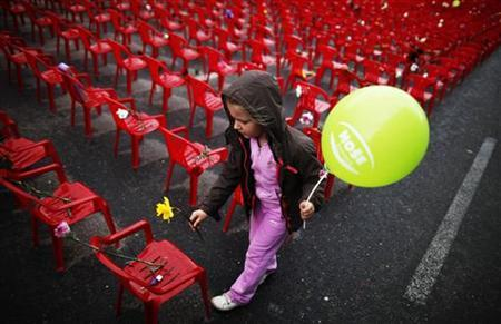 A child puts flowers on one of the 11,541 red chairs along Titova street in Sarajevo, as the city marks the 20th anniversary of the start of the Bosnian war, April 6, 2012. REUTERS/Dado Ruvic