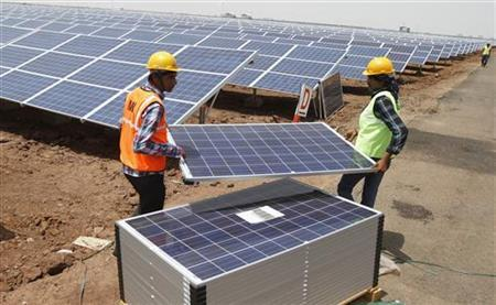 Workers carry photovoltaic solar panels for installation at the Gujarat solar park under construction in Charanka village in Patan district of Gujarat April 14, 2012. REUTERS/Amit Dave