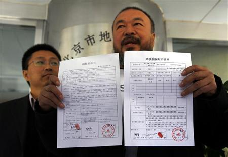 Dissident Chinese artist Ai Weiwei holds his tax bond agreement slips, next to his company accountant Du Yanlin, as they leave the Beijing government tax bureau November 16, 2011. REUTERS/David Gray