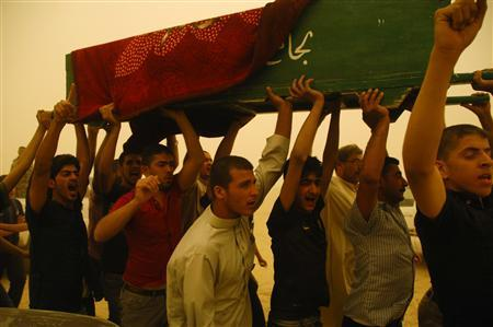 Residents carry the coffin of a victim who was killed in a bomb attack in Samarra, 100 km (62 miles) north of Baghdad, as a sandstorm rages April 19, 2012. REUTERS/Bakr al-Azzawi
