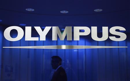 A man walks behind a logo of Japan's Olympus Corp at the company headquarters in Tokyo in this April 3, 2012 file photo. REUTERS/Yuriko Nakao/Files