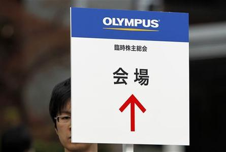 A man holds a signboard which reads ''Olympus Corp extraordinary shareholders' meeting venue'' near the venue in Tokyo April 20, 2012. REUTERS/Toru Hanai