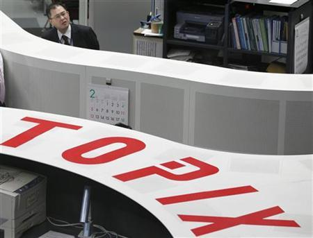 An employee of the Tokyo Stock Exchange looks at a board, of which some listed companies stock prices are not shown, at the bourse of its headquarters in Tokyo February 2, 2012. REUTERS/Kim Kyung-Hoon/Files