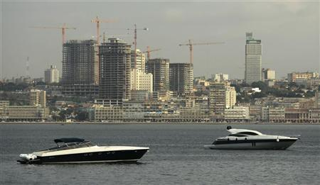 Speedboats sit beneath the backdrop of Luanda January 27, 2010. REUTERS/Rafael Marchante