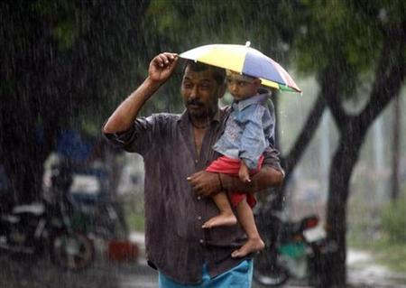 A man carrying a child tries to cover himself with the child's umbrella while walking during heavy downpour in Noida, in the outskirts of New Delhi September 16, 2011. REUTERS/Parivartan Sharma/Files