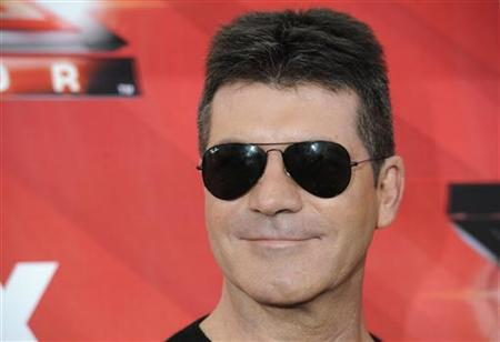Judge Simon Cowell poses for photographers following a news conference for the television show ''The X Factor'' held in Los Angeles December 19, 2011. REUTERS/Phil McCarten