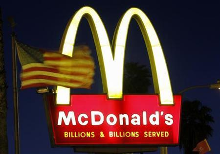 A U.S. flags flutters in the wind in front of a sign for a McDonald's restaurant in Los Angeles April 4, 2011. . REUTERS/Mario Anzuoni