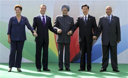 (From L-R) Brazil's President Dilma Rousseff, Russian President Dmitry Medvedev, Indian Prime Minister Manmohan Singh, Chinese President Hu Jintao and South African President Jacob Zuma join their hands together during a group photo for the BRICS Summit in New Delhi March 29, 2012. REUTERS/B Mathur