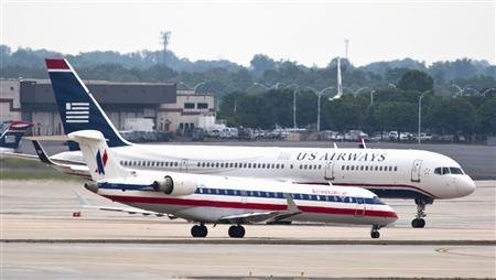 A US Airways jet taxies to the runway as an American Airlines jet waits on the tarmac in Charlotte, North Carolina April 20, 2012. REUTERS/Chris Keane