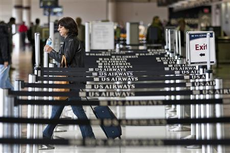 A US Airways passenger walks away after checking in for her flight at Charlotte Douglas International Airport in Charlotte, North Carolina April 20, 2012. REUTERS/Chris Keane