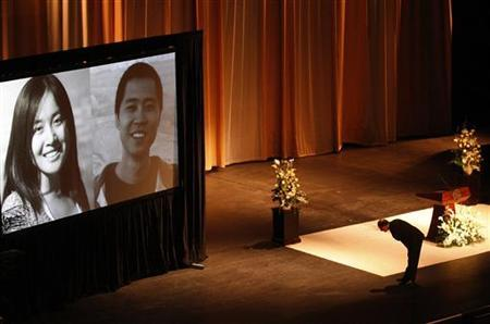 USC (University of Southern California) president C. L. Max Nikias bows before images of Chinese murder victims Ying Wu and Ming Qu before eulogizing the slain engineering students during a memorial service in the Shrine Auditorium in Los Angeles April 18, 2012. Victims Ming Qu and Ying Wu, engineering students at USC, were killed April 11, 2012, as they were attacked while sitting in their parked car near campus. REUTERS/Luis Sinco/Pool