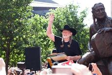Singer Willie Nelson waves beside a statue of himself during its unveiling in downtown Austin, Texas April 20, 2012. REUTERS/Julia Robinson